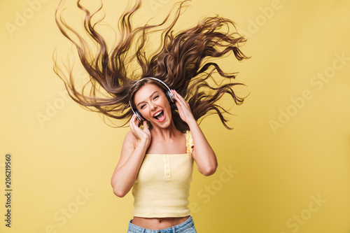 Foto  Image of amusing woman 20s singing and having fun with shaking hair while listen