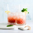 pink non-alcoholic mocktail made from grapes with lemon and mint and shaker . summer refreshing drink