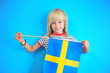 Cute blonde hair kid holding flag of Sweden
