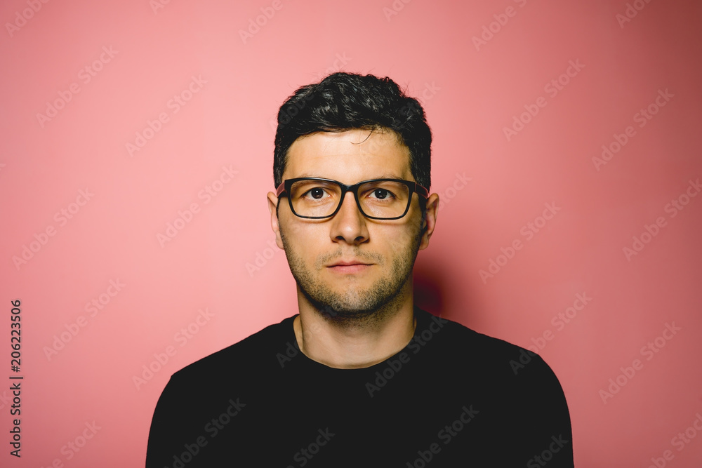 Young man with eyeglasses on pink background