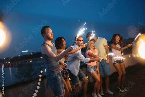 Happy friends lighting sparklers and enjoying freedom
