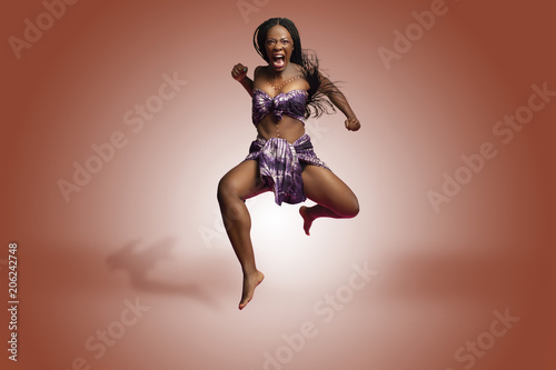Küchenrückwand aus Glas mit Foto Tanzschule Beautiful African Black girl wearing traditional colorful African outfit does a dramatic aggressive leaping dance move against a colorful brown background