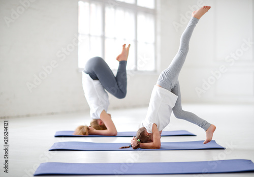 Valokuvatapetti mother with child practicing yoga in headstand