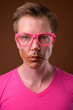 Young handsome man wearing pink shirt and eyeglasses against bro