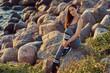 Portrait of a beautiful brunette fitness woman in a gray sportswear sitting on a rock by a sea.