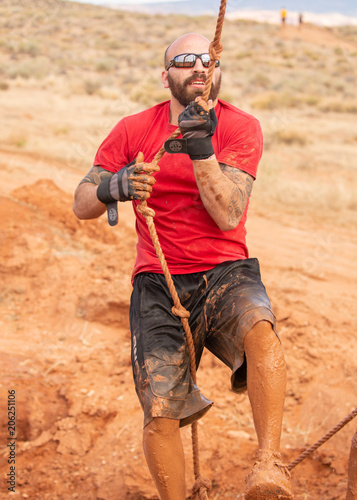 Fotografie, Obraz  A man in sunglasses and a red shirt climbing up out of a mud pit during a mud ru
