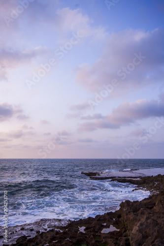 Fotobehang Purper Smooth waves on a calm beach sunset