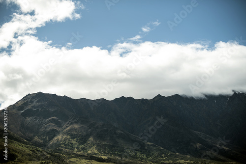 Spoed Foto op Canvas Grijze traf. Landscape of shady mountains with huge clouds over them. day shot with blue sky.