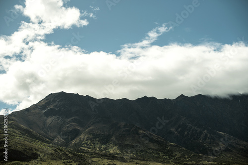 Landscape of shady mountains with huge clouds over them. day shot with blue sky.
