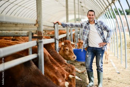 Leinwand Poster portrait of handsome farmer in a livestock small breeding husbandry farming prod