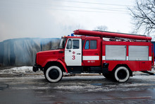 Chernivtsi / Ukraine - 03/19/2018: Fire Engine With Sirens And Blue Lights With Fire On Background.