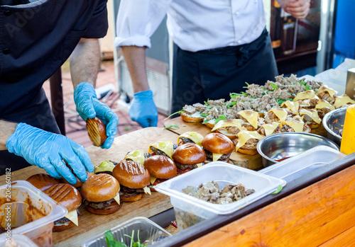 Fototapeta Street fast food. Cooks prepare different burgers in outdoors obraz