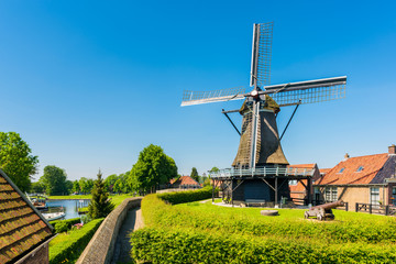 Windmill in the village of Sloten, Friesland, Netherlands on spring day