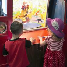 Kids At Penny Arcade Watching Circus Clown Game