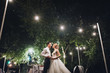 canvas print picture - Beautiful newlyweds stand, holding hands, at a wedding party with lamps. Stylish wedding ceremony.