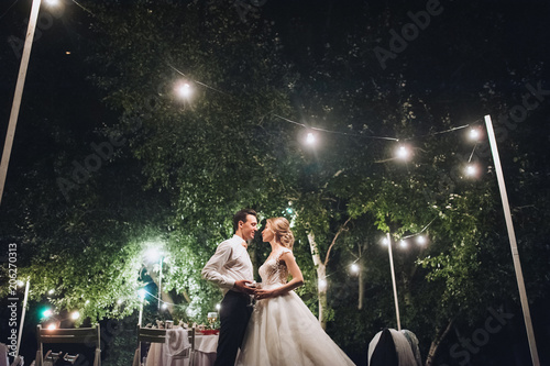 Fotografía  Beautiful newlyweds stand, holding hands, at a wedding party with lamps
