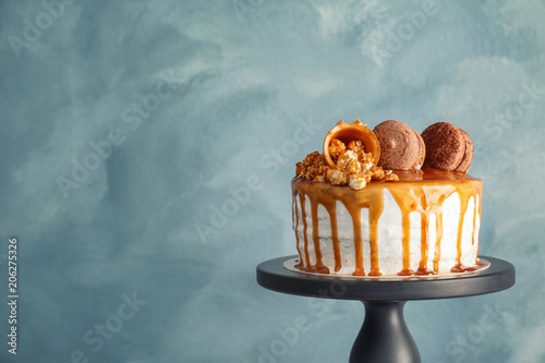 Staande foto Macarons Dessert stand with delicious caramel cake on color background