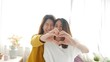 Young asian lesbian LGBT couple forming heart shape with hands on bedroom at home.