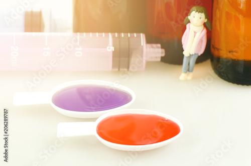 Fotografie, Obraz  Syrup medication in teaspoon with oral syringe and medicine bottle background