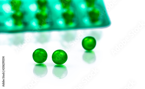 Green round soft capsule pills on blurred background of blister pack