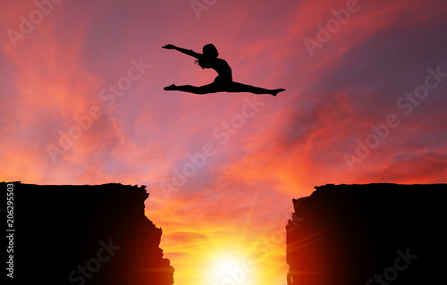 Fotobehang Jacht Silhouette of Girl Leaping Over Cliffs With Sunset Landscape