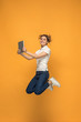 Image of young woman over orange background using laptop computer or tablet gadget while jumping.