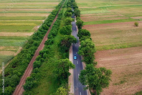 Tuinposter Luchtfoto Aerial view over the road with trees on the both sides in the middle of the field and cars driving