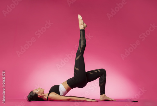Fotografie, Obraz Long haired beautiful pilates or yoga athlete does a graceful pose while wearing