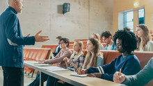 Professor Holding Lecture To A Multi Ethnic Group Of Students. Smart Young People Studying At The University.
