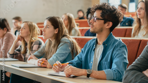 Photo  In the Classroom Multi Ethnic Students Listening to a Lecturer and Writing in Notebooks