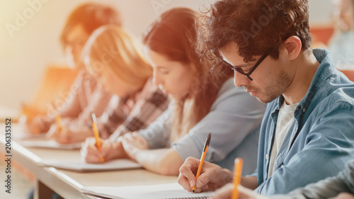 Fotografia  Moving Footage of a Row of Multi Ethnic Students in the Classroom Taking Exam/ Test
