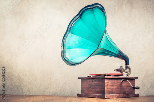 Photo Vintage aged turquoise gramophone phonograph turntable on wooden table front concrete wall background