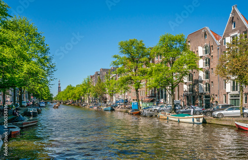 Poster Amsterdam Amsterdam, May 7 2018 - The Prinsengracht with small boats sailing on it and in the background the Westertoren on a sunny day