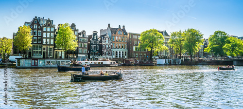 Photo Stands Amsterdam Amsterdam, May 7 2018 - view on the river Amstel filled with small boats and traditional houses in the background on a summer day