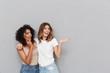 Leinwandbild Motiv Portrait of two cheerful young women standing together