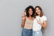 canvas print picture - Portrait of two cheerful young women standing together