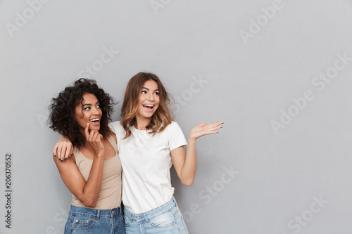 Carta da parati Portrait of two cheerful young women standing together