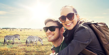 Travel, Tourism And People Concept - Happy Couple With Backpacks Having Fun Over African Savannah And Zebras Background