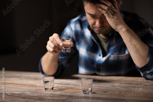 Fotografija  alcoholism, alcohol addiction and people concept - male alcoholic drinking shot