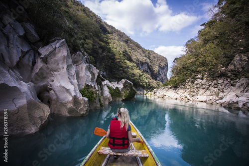 Rear view of woman sitting in boat on river amidst mountains against sky
