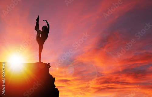 Fotobehang Baksteen Silhouette of Girl Exercising on Edge of Cliff at Sunrise