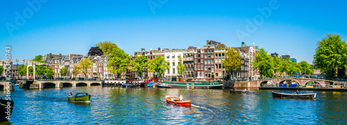 La pose en embrasure Amsterdam Amsterdam, May 7 2018 - view on the river Amstel filled with small boats and the Magere brug (skinny bridge) in the background on a summer day