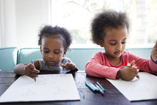 Sisters Drawing With Crayons On Papers At Home