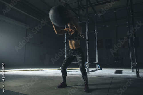 Female athlete exercising with fitness ball in gym