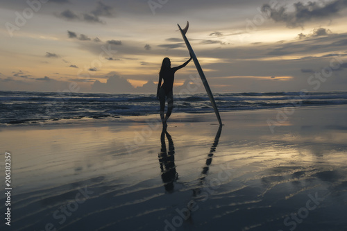 Full length of silhouette young woman with surfboard standing at beach against sky during sunset
