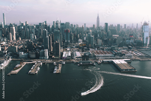 Aerial view of cityscape by Hudson river against sky during sunny day