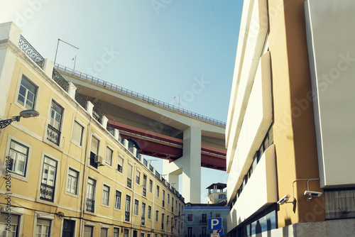 Typical street of Lisbon (Portugal) under a huge bridge. Photograph taken on daylight with a clear blue sky.