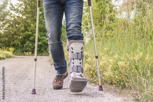Fotografia Mann läuft mit einer Orthese und Gehhilfen über einen Feldweg
