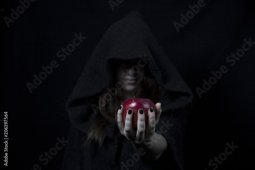 Fototapeta  Snow white's red apple in the hand of a black witch with black painted nails