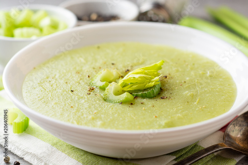 Celery cream soup in white plate on gray stone background